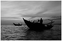 Men on fishing skiffs under bright sunset skies. Mui Ne, Vietnam (black and white)