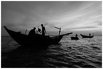 Fishermen on boats at sunset. Mui Ne, Vietnam (black and white)