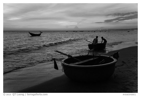 Fishermen bringing round coracle boat to shore at sunset. Mui Ne, Vietnam (black and white)
