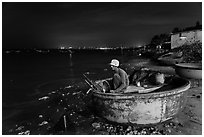 Man working on coracle boat at night. Mui Ne, Vietnam (black and white)