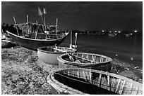 Coracle boats and fishing fleet at night. Mui Ne, Vietnam (black and white)