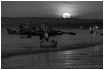 Fisherman paddling on coracle boat towards fishing boats at moonset. Mui Ne, Vietnam (black and white)