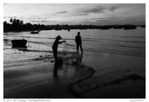 Woman collecting fishing net at dawn. Mui Ne, Vietnam (black and white)