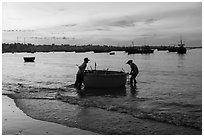 Fishermen pushing coracle boat at dawn. Mui Ne, Vietnam (black and white)