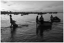 Fishermen using coracle boats to transport cargo at dawn. Mui Ne, Vietnam (black and white)