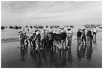 Women gather on beach to collect freshly caught fish. Mui Ne, Vietnam (black and white)
