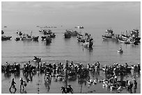 View from above of fishermen, vendors, and fishing fleet. Mui Ne, Vietnam (black and white)