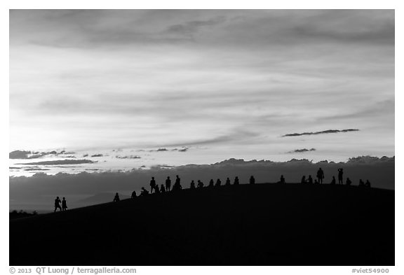 Tourists on dune ridge at sunset. Mui Ne, Vietnam (black and white)