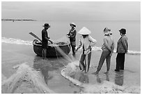 Fishermen, net, and coracle boat. Mui Ne, Vietnam (black and white)