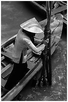 Woman in Ao Ba Ba holding from boat to bamboo poles. My Tho, Vietnam ( black and white)