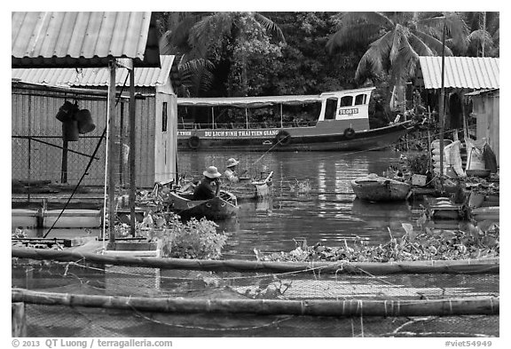Men fishing next to houseboats. My Tho, Vietnam (black and white)