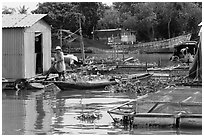 Man paddling out of houseboat. My Tho, Vietnam ( black and white)