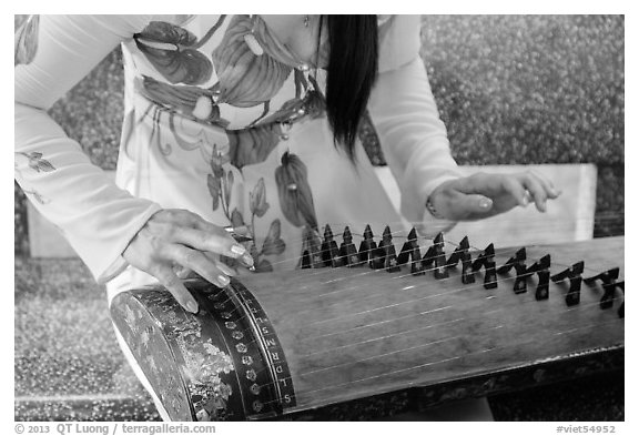 Close up of hands playing plucked zither. My Tho, Vietnam (black and white)
