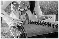 Close up of hands playing plucked zither. My Tho, Vietnam ( black and white)