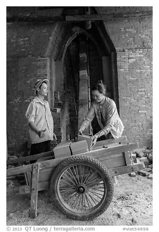 Workers loading bricks out of brick oven. Mekong Delta, Vietnam (black and white)