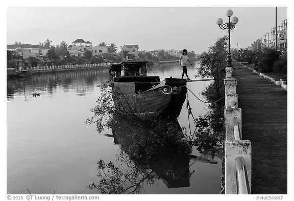 Woman in high heels walking out of barge. Tra Vinh, Vietnam (black and white)