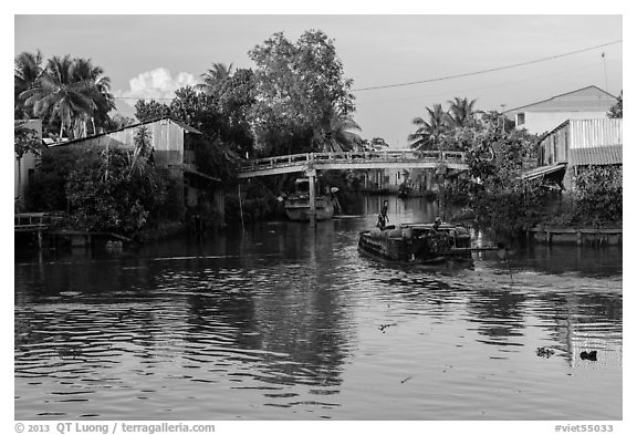 Barge and canal-side houses. Mekong Delta, Vietnam (black and white)