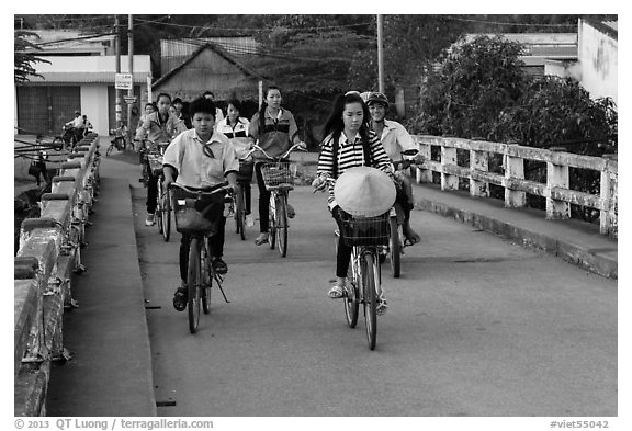 Children bike on way to school, Phung Diem. Can Tho, Vietnam (black and white)