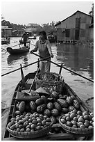 Woman paddles boat loaded with fruits and vegetable, Phung Diem. Can Tho, Vietnam ( black and white)