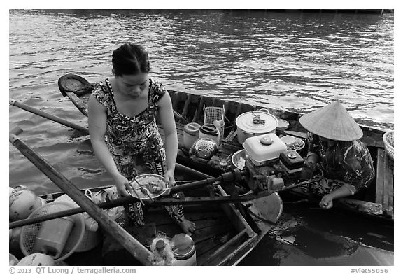 Woman gets bowl of noodles from floating market. Can Tho, Vietnam (black and white)