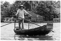 Woman using the distinctive x-shape paddle. Can Tho, Vietnam (black and white)