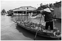 Woman paddling boat loaded with bananas. Can Tho, Vietnam (black and white)