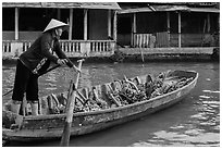 Woman paddling sampan boat loaded with bananas. Can Tho, Vietnam (black and white)