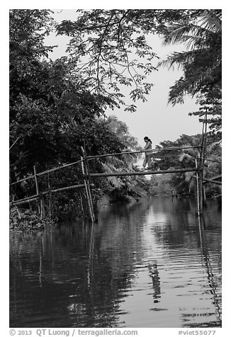 Woman walking across monkey bridge. Can Tho, Vietnam (black and white)