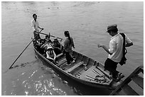 Schoolchildren stepping onto boat. Can Tho, Vietnam (black and white)