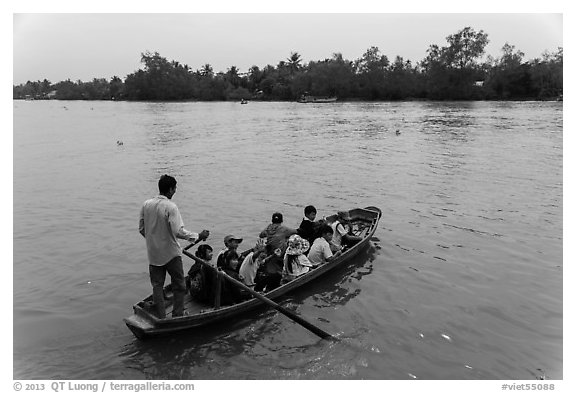Schoolchildren crossing river on boat. Can Tho, Vietnam (black and white)