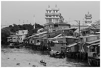 Riverside houses on stilts and Cao Dai temple. Mekong Delta, Vietnam ( black and white)