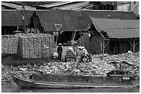 Workers loading bricks on boat. Sa Dec, Vietnam (black and white)
