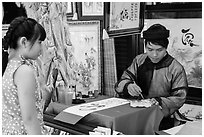 Caligrapher draws Tet greetings as woman looks on. Ho Chi Minh City, Vietnam ( black and white)