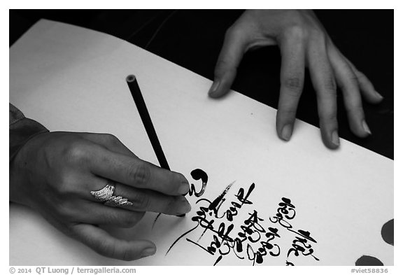 Feminine hand draws Lunar New Year greetings in fancy writing. Ho Chi Minh City, Vietnam (black and white)