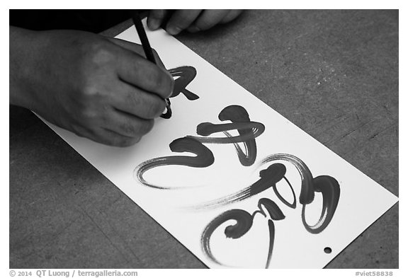 Hands drawing Tet (Lunar New Year) greetings in Chinese characters. Ho Chi Minh City, Vietnam (black and white)