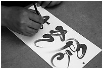 Hands drawing Tet (Lunar New Year) greetings in Chinese characters. Ho Chi Minh City, Vietnam ( black and white)