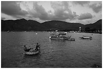 Men in coracle boat paddling in Con Son harbor. Con Dao Islands, Vietnam ( black and white)