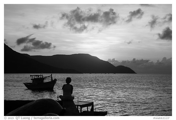 Silhouetted woman watching sunrise from Wharf 914, Con Son. Con Dao Islands, Vietnam (black and white)