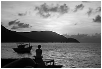 Silhouetted woman watching sunrise from Wharf 914, Con Son. Con Dao Islands, Vietnam ( black and white)