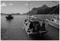 Sailor throws rope from boat, Ben Dam harbor. Con Dao Islands, Vietnam ( black and white)