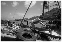 Man scoops ice into fishing boat, Ben Dam. Con Dao Islands, Vietnam ( black and white)