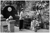 Woman offers incense at Vo Thi Sau grave. Con Dao Islands, Vietnam ( black and white)