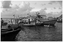 Fishing boats and man standing on raft, early morning, Con Son harbor. Con Dao Islands, Vietnam ( black and white)