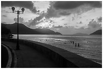 Seafront promenade and beachgoers at sunrise, Con Son. Con Dao Islands, Vietnam ( black and white)