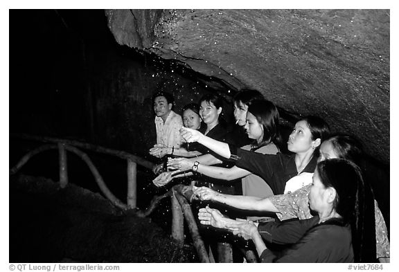 Women catch the water seeping from Tan Thanh Cave, said to have mirculous properties. Lang Son, Northest Vietnam (black and white)