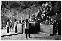 Women praying at the altar at the entrance of Tan Thanh Cave. Lang Son, Northest Vietnam (black and white)