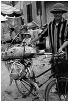Man with a newly bought pig loaded on his bicycle, That Khe market. Northest Vietnam (black and white)