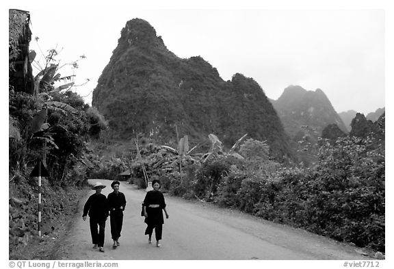 Villagers in traditional garb walking down the road with limestone peaks in the background, Ma Phuoc Pass area. Northeast Vietnam (black and white)