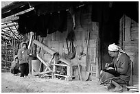 Elderly woman sewing  on her doorstep as kids look up. Northeast Vietnam ( black and white)