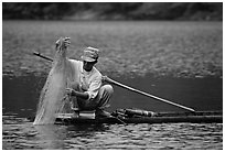 Fisherman retrieves net from a dugout boat. Northeast Vietnam (black and white)